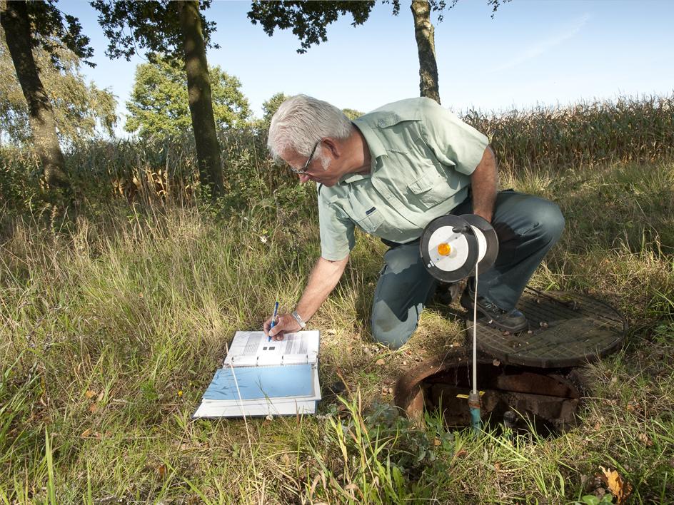waterkwaliteit wordt in een put gemeten door man met apparatuur