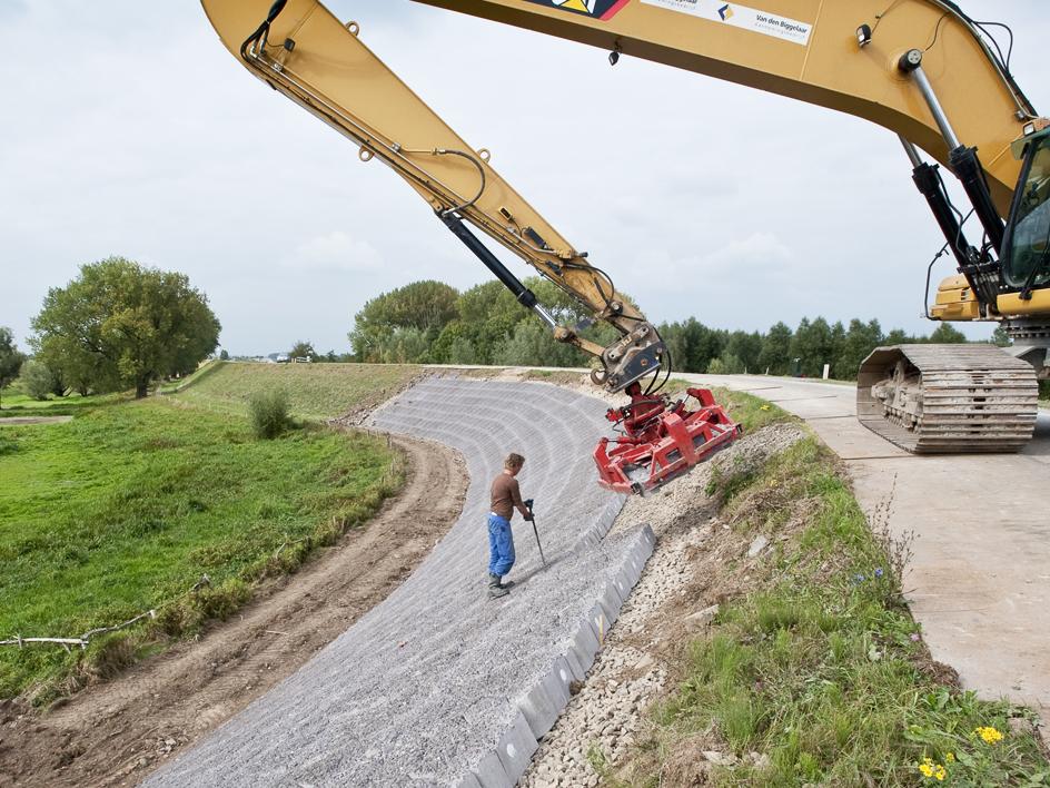 dijkversterking door nieuwe stenen machinaal aan te brengen aan de zijwanden van de dijk